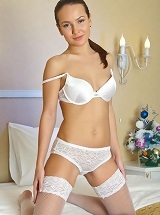 Gloria's exotic princess and elegant, smooth body stands out as she strips her erotic white underwear matching thigh-high nylons on the bed.